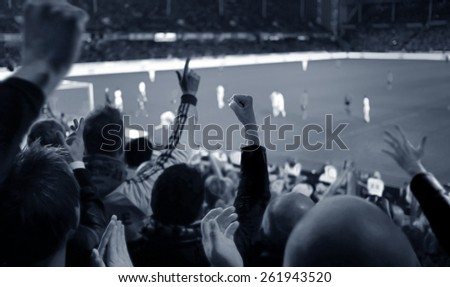Fans excited at a football game, selective focus on fans with hands raised - stock photo