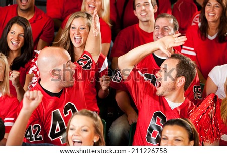 Fans: Friends Give High Five When Team Scores Touchdown - stock photo