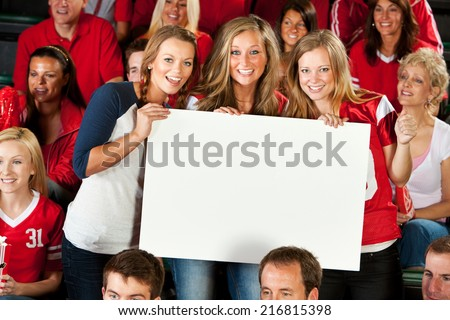 Fans: Group Of Girls Holds Up Blank Sign At Football Game - stock photo