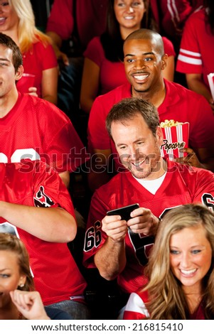 Fans: Man Looking At Phone During Football Game - stock photo
