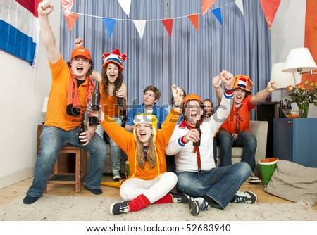 Fans of one team cheer, with their friends, supporting the opposite team look in disbelief - stock photo