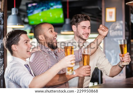 Fans watching football on TV. Three cheerful friend clink beer at the bar and drink a beer while the bartender is standing on the bar. Friends having fun together - stock photo