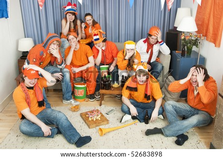 Fans, watching their national team on the couch at home being horrified with the events on screen - stock photo
