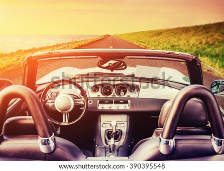 Fantastic asphalt road along the sea to the west. The car with folding roof. - stock photo