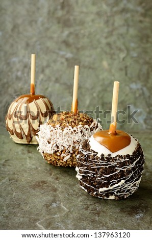 Fantastic candied carmel apples on green slate - stock photo
