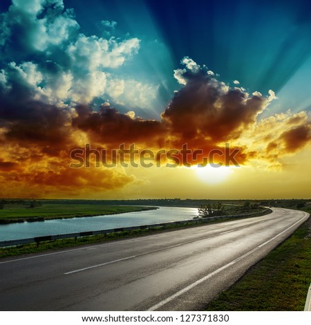 fantastic dramatic sunset over asphalt road - stock photo