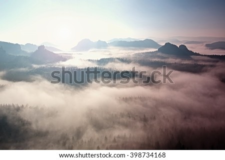 Fantastic dreamy sunrise on the top of the rocky mountain with the view into misty valley. Beautiful day in nature - stock photo