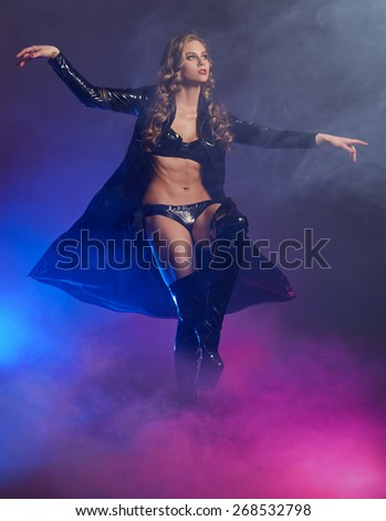 Fantastic female dancer in glow of purple smoke - stock photo