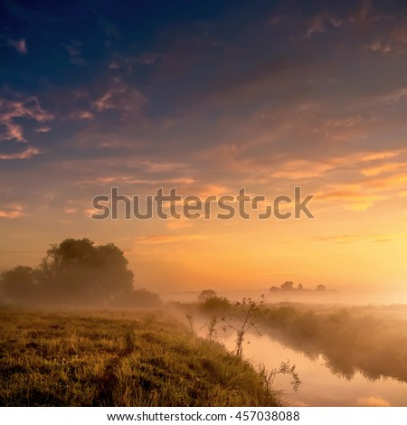 Fantastic foggy river with fresh grass in the sunlight. majestic misty sunrise with colorful clouds on the sky,    Dramatic unusual scene. Warm sundown over meadow. Beauty in the world. - stock photo