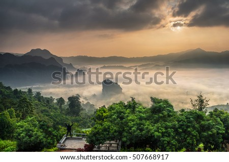 Fantastic Landscape of Misty Mountain when sunrise which have A man standing and Hands up over Phu Lanka mountain hills, Phayao province, north of Thailand.