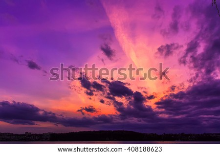 fantastic landscape. The dramatic scene sunset over a lake, rays erupt through the heavy storm clouds reflected in the water. color in nature.