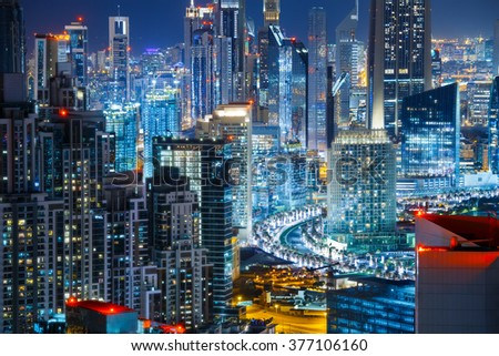Fantastic rooftop view of illuminated city architecture by night. Business bay, Dubai, United Arab Emirates. Travel and nightlife concept.