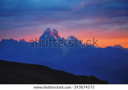 Fantastic sunlight over of Mt. Ushba. Dramatic and picturesque morning scene. Location famous resort  Mestia, Upper Svaneti, Georgia, Europe. High Caucasus ridge. Artistic picture. Beauty world.