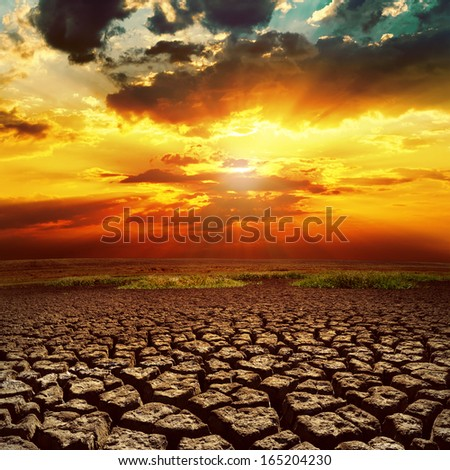 fantastic sunset over cracked earth - stock photo