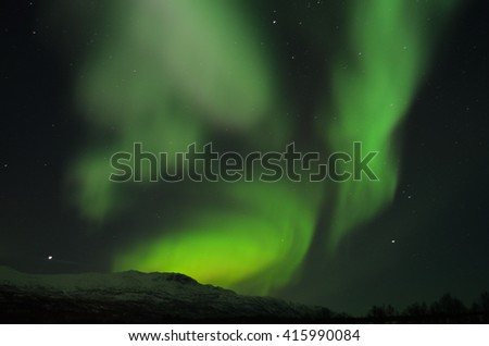 Fantastic vibrant and strong aurora borealis, northern light over snow covered mountain and frozen river bed in the arctic circle at night