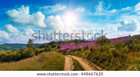 fantastic view. ideal sky with clouds. over mountain road and field with lupin flowers. picturesque scene. breathtaking scenery. wonderful landscape. use as background. original creative images - stock photo
