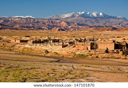 Fantastic view of a ksar between Ouarzazate and Ait Ben Haddu, illuminated by sunset. Snowy Atlas mountains in the background. - stock photo