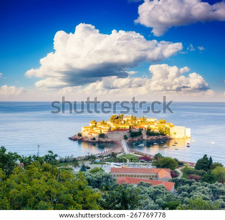 Fantastic view of the Sveti Stefan, small islet and resort in Montenegro. Dramatic morning scene. White fluffy clouds. Balkans, Adriatic sea, Europe. Beauty world.  - stock photo