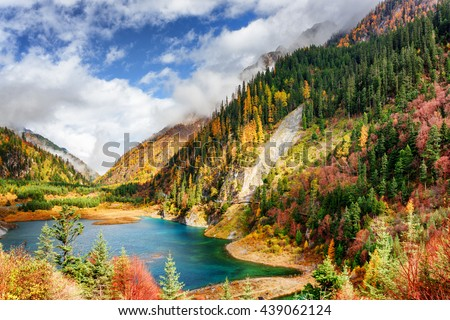 Fantastic view of the Upper Seasonal Lake with azure water among colorful fall woods and mountains in fog, Jiuzhaigou nature reserve (Jiuzhai Valley National Park), China. Scenic autumn landscape.