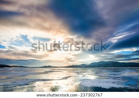 Fantastic winter landscape with frozen lake. Beautiful sunset with dramatic sky