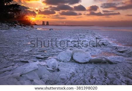fantastic winter sunset on the frozen lake in broken ice - stock photo