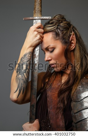 Fantastic woman warrior with sword. Isolated on a grey background - stock photo