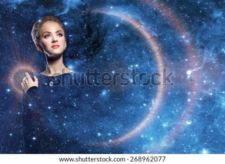 Fantastic woman with diamonds on a background of blue radiance space sky decorated with lots of stars. Fantastic night landscape. Stellar beauty of a woman in the rays of light planets and space.
