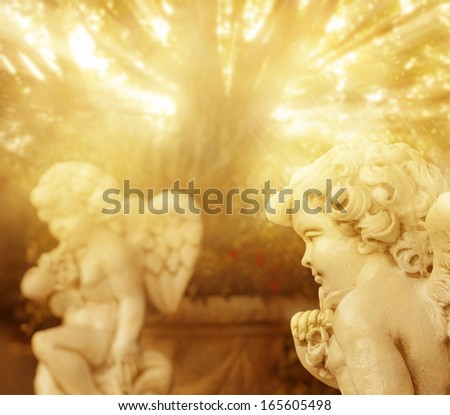 Fantastical portrait of angelic cherub statues with rays of golden light - stock photo