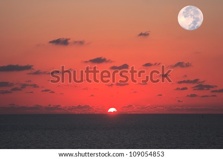 Fantastically beautiful sunset on the Mediterranean Sea. At the same time see the sun and the moon