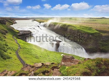 Fantastically spectacular cascading waterfall Gyullfoss. On the coastal slope paved walking trail - stock photo