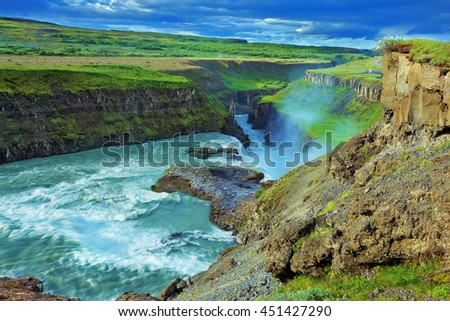Fantastically spectacular cascading waterfall Gyullfoss. Roaring water glistens on the northern sun. Iceland in the summer - stock photo