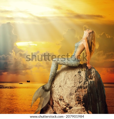Fantasy. beautiful woman mermaid with fish tail and long developing hair - stock photo