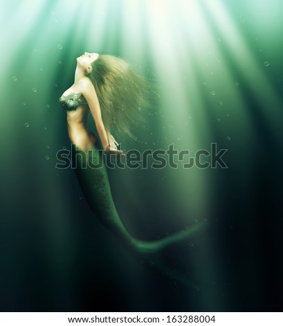 Fantasy. beautiful woman mermaid with fish tail and long developing hair swimming in the sea under water - stock photo