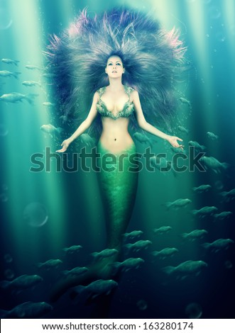 Fantasy. beautiful woman mermaid with fish tail and purple hair swimming in the sea under water - stock photo