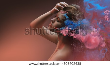 Fantasy beauty fashion model face closeup inside colorful paint in shape of abstract clouds. Design with Water color spreading underwater. Fantastic shapes in orange background. - stock photo