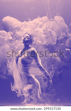 Fantasy fashion model inside ultraviolet clouds. Paint spreading underwater. Abstract shapes in space. - stock photo