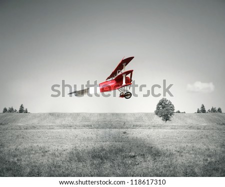 Fantasy flight of an old red airplane flying on a field and sky in black and white - stock photo