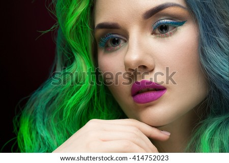 Fantasy girl. Cropped closeup of a beautiful green and blue haired woman wearing purple lipstick against black background