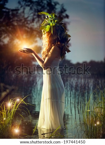 Fantasy girl taking magic light in her hands. Mysterious Night scene. Witch standing in the river and practice witchcraft. Fairytale - stock photo