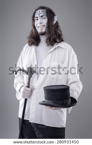 Fantasy Illusionist Performer. Body painted performer in black and white suit with hat and stick.  - stock photo