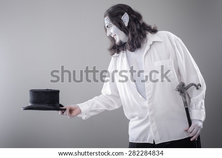 Fantasy Illusionist Performer Bowing. Body painted performer in black and white suit bowing with hat and stick  - stock photo