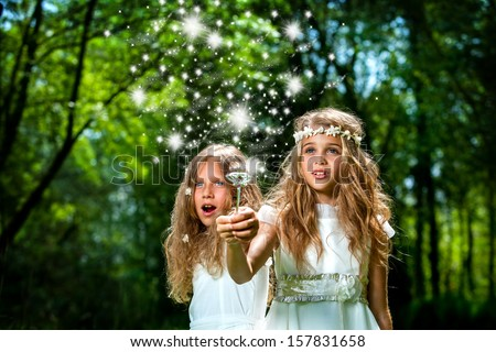 Fantasy portrait of cute girls with magic wand in forest. - stock photo