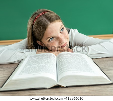 Fantasy pupil looking up as if daydreaming or thinking of something pleasant while sitting at the desk with open book. Photo of teen school girl, creative concept with Back to school theme - stock photo