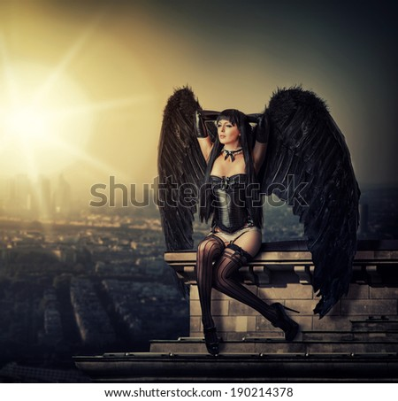 Fantasy shot - female black angel with wings sitting on  roof of a building in city at sunrise - stock photo