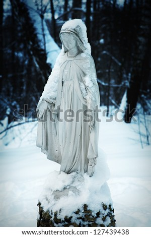 Fantasy shot of snow-covered Religious sculpture in the courtyard of small town church - stock photo