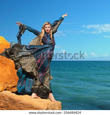 Fantasy style portrait of woman in blue dress at the seashore - stock photo