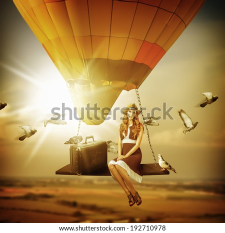 Fantasy travel. Young woman flying a balloon - stock photo