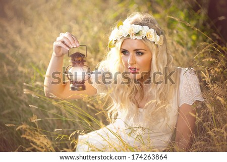 Fantasy whimsical image of beautiful woman in field holding lamp, wearing flowers in her hair - stock photo