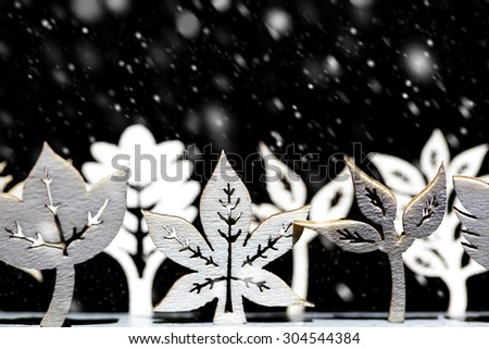 Fantasy winter snow scene with a line of artistic white trees and leaf shapes all under a heave snowfall - stock photo