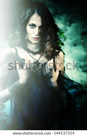 fantasy woman in garden with black veil and sun light small amount of grain added - stock photo